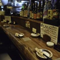 黒糖焼酎が並ぶ飲食店のカウンター=25日、奄美市名瀬