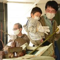 手熟師会の子ども講習会で黒糖作りを体験する参加者=24日、奄美市笠利町