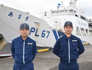 巡視船あまぎと今年3月退官予定の溜さん(左)、昨年9月に着任したばかりの青山さん=20日、奄美市の名瀬港観光船バース