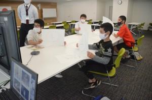 奄美大島の6会場をつないだオンラインの画面に向かい、クイズに参加する奄美市名瀬会場の児童生徒たち=23日、奄美市名瀬の名瀬総合支所