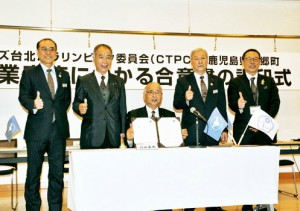 東京五輪・パラリンピック後の交流に向け合意書に調印した竹田町長(中央)ら=9日、龍郷町