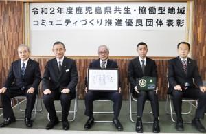 田中支庁長(左から2番目)から賞状の伝達を受けた奄美通信システムの椛山社長ら(中央)=15日、奄美市名瀬