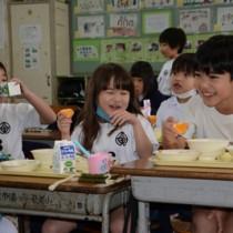 提供されたタンカンを頬張る児童=17日、奄美市名瀬の奄美小学校