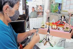ひな人形の着物を紬に着せ替える作業をする重山さん=14日、瀬戸内町古仁屋