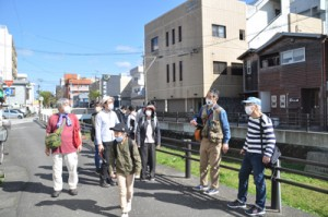 西條さん(右から2番目)の案内で市街地を散策する参加者ら=20日、奄美市名瀬