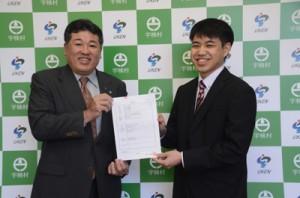 元山公知村長(左)から地域おこし協力隊の委嘱状を受け取る栄雄大さん(右)=1日、宇検村役場