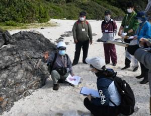 成尾さん(左)の説明を受け、地質の成り立ちについて学ぶ参加者=21日、徳之島町金見