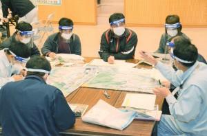 湯湾~石良集落を歩いて点検したマップをもとに、課題点などを話し合う村民たち=17日、宇検村湯湾の元気が出る館