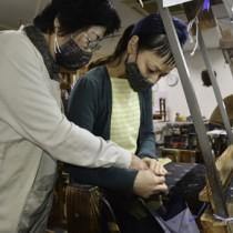 機織りの指導を行う伝統工芸士の平さん(左)と受講生の石川さん=1月23日、龍郷町大勝の夢おりの郷