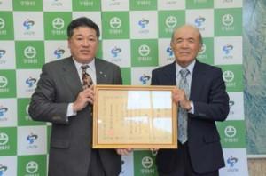 元山公知村長から農林水産大臣表彰を受け取った俊岡章一さん(右)=5日、宇検村役場