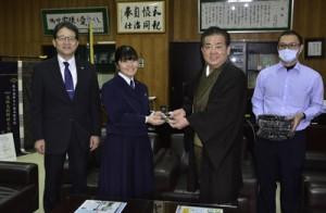 卒業記念品を手渡す牧理事長(右から2人目)と受け取る大島高校の箕輪さん=2日、奄美市名瀬