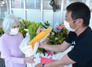 沖永良部島産の花束をプレゼントする知名町農業青年クラブのメンバー(右)=14日、知名町