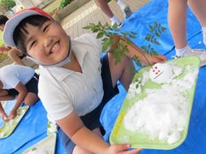 雪うさぎを作り、笑顔を見せる児童(提供写真)