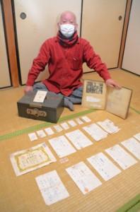 父の遺品から出てきた米軍統治下の資料を広げる西村勝博さん=1月7日、奄美市名瀬佐大熊町