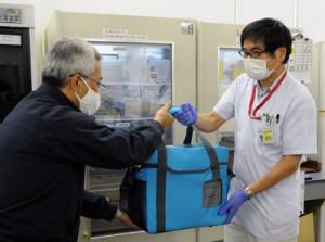 訓練で、模擬血液製剤を入れた血液搬送用冷蔵庫をタクシー運転手(左)に託す県立大島病院中央検査部の職員=16日午後7時ごろ、奄美市名瀬の同病院