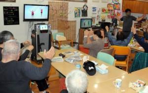 デイサービスで動画に合わせて体操する利用者(資料写真)
