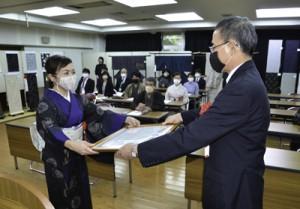 本場奄美大島紬産地まつりで表彰状を受け取る南さん=17日、奄美市名瀬