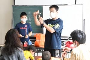 ゴム鉄砲の作り方を教える満想さん(右)と基さん=14日、奄美市名瀬の奄美博物館