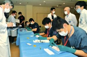 先輩医師が採点する中、外科技術を競う研修医たち=3日、奄美市名瀬