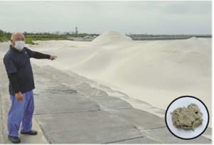 搬入された人工ビーチ用の砂を指差す与論町漁協の阿多組合長=4日、与論町