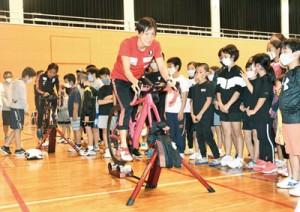 リズムに合わせてバイクをこぐ練習方法を紹介する井出さん(中央)と蔵本さん=7日、伊仙町伊仙