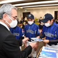 朝山市長(手前)からベイスターズのプレゼントを受け取る児童ら=3日、奄美市役所