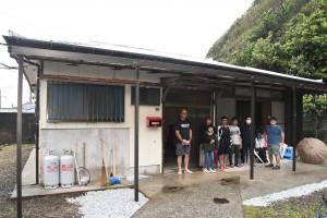 改修された空き家と移住してきた鈴木さん親子(左から2番目の2人)ら=28日、大和村名音