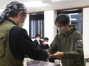 奄美大島エコツーリズム推進協議会の喜島会長(左)から証書を受け取る新規認定者=30日、奄美市名瀬