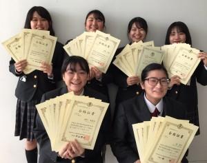 樟南第二高校で初となる全商検定7種目1級を取得した德さん(前列右)と各種目で1級合格を果たした卒業生(提供写真)