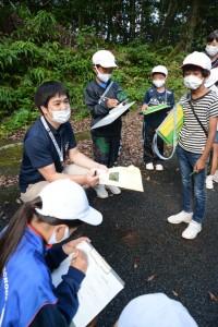 篠川小中学校の児童生徒に三太郎峠のフィールドワークで動植物の開設をする平城さん=2020年10月、奄美市住用町