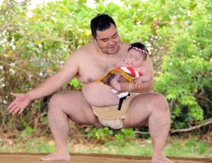 父親に抱かれて土俵入りする男児=21日、瀬戸内町