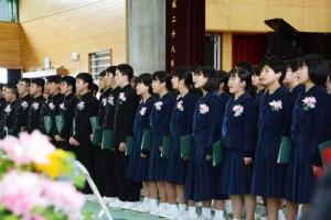 涙をこらえて最後の合唱に臨む卒業生=16日、奄美市名瀬の金久中学校