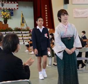 温かい拍手の中、会場を後にする元山絆君=24日、大和村