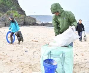 佐仁海岸で漂着ごみを回収する参加者たち=7日、奄美市笠利町