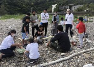 海岸で拾ったごみで楽器作りをする参加者=14日、瀬戸内町(主催者提供)