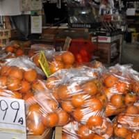 袋詰めで青果店に山積みされているタンカン=2日、奄美市名瀬