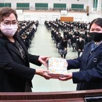 徳之島町の職員からクロウサギと共に育ったタンカンを受け取る徳之島高校の生徒(前列右)=1日