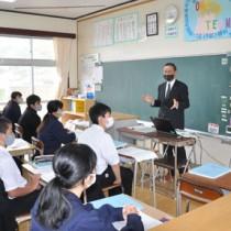 奄美の魅力について講演する田中完大島支庁長(右)=2月26日、奄美市名瀬の金久中学校