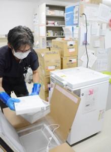 超低温冷凍庫に移すため、ワクチンが入った箱を取り出す病院関係者=27日、沖永良部徳洲会病院