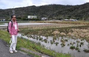 スマホから流れる観光案内を聞きながら秋名集落の田んぼ道を歩く勝さん=1日、龍郷町