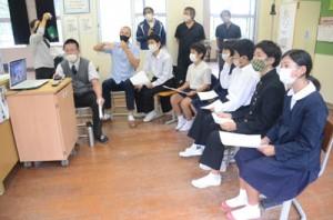 教室に設置されたパソコンとテレビの大画面に向かい、宇検村の生活について説明する久志小中学校の児童生徒たち=16日、宇検村久志