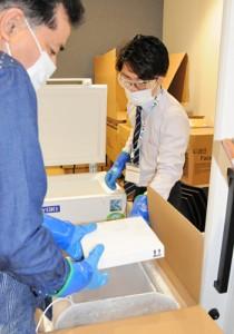 超低温冷凍庫に移すため、ワクチンが入った箱を取り出す市の担当職員=7日、奄美市