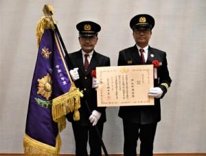 消防庁長官表彰で表彰旗が授与された伊仙著消防団の樺山団長(右)と佐倉功一副団長=27日、鹿児島市