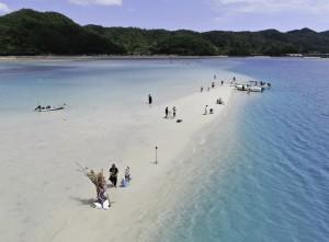姿を現した「かくれ浜」で海遊びする住民ら=28日、奄美市笠利町の喜瀬沖(本社小型無人機で撮影)