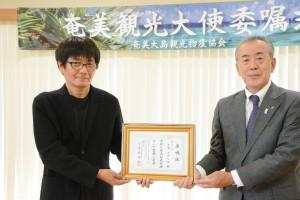 奄美観光大使の委嘱状を受け取る荒木さん(左)=28日、奄美市名瀬