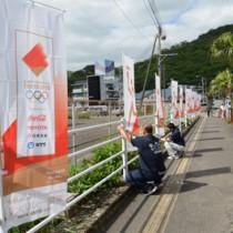 聖火リレーコース沿道にのぼりを設置する市職員ら=6日、奄美市名瀬