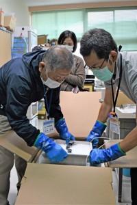 新型コロナウイルスワクチンを箱から取り出す大和診療所の職員=10日午前10時58分、大和村