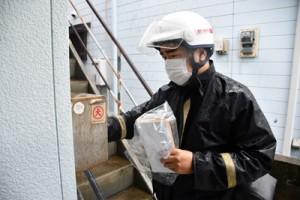 高齢者への新型コロナワクチン接種に関する書類を各世帯に届ける郵便局職員=2日、大和村大和浜