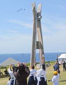 慰霊飛行するF15戦闘機を見送る慰霊祭参列者