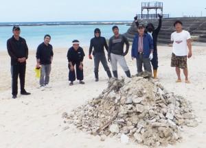 天城町のヨナマビーチを清掃した徳之島観光連盟の会員と回収した岩や石=25日、同町